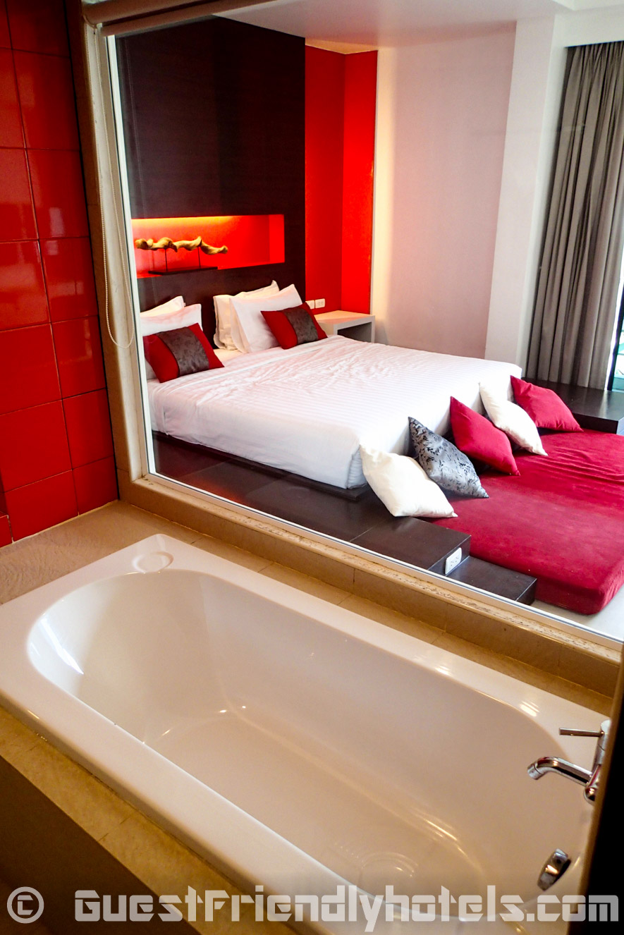 Open glass bathroom with tub and shower seperate inside Alfresco Phuket Hotel